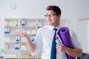 Mann mit Krawatte und Yogamatte im Büro